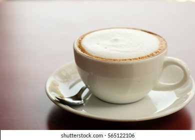Cappuccino coffee on wooden table and sunlight background