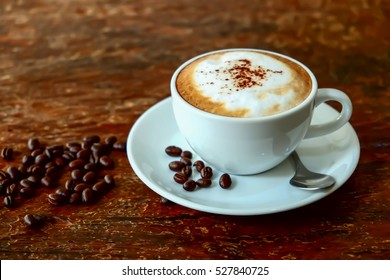 Cappuccino coffee and roasted coffee beans on wooden table and vivid color background