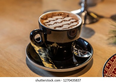 Cappuccino coffee served in a black cup with a cream in artistic style