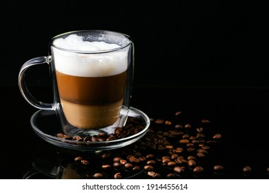 Cappuccino coffee in a transparent cup on a black background and scattered coffee beans.