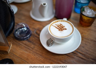 Cappuccino coffee in white ceramic pot on wooden table, surrounding with glass cup and tea pot.