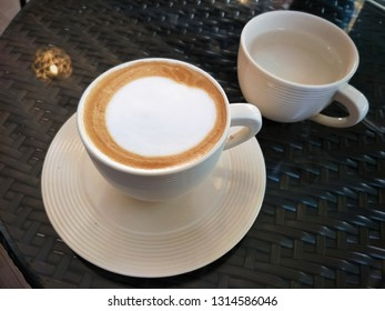 Cappuccino cofffee in ceramic cup and Saucer on table.