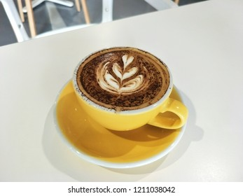 Cappuccino cofffee in yellow ceramic cup and Saucer on table.