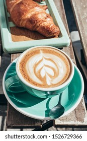 Cappuccino and croissant at a cafe in the morning