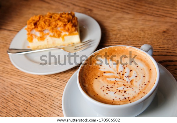 cappuccino cup with cheesecake on the brown wooden table