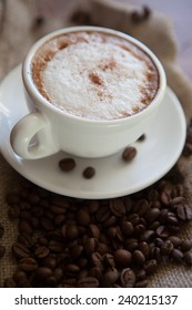 Cappuccino cup with coffee beans