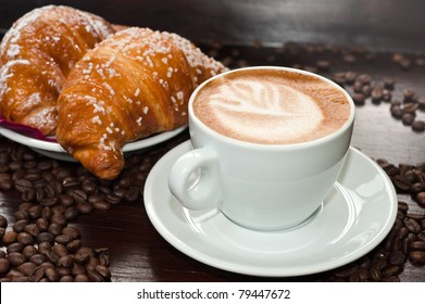 Cappuccino in a cup with croissant and coffee beans