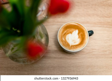 Cappuccino cup with flowers on wooden table shot from above
