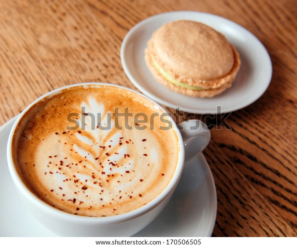 cappuccino cup with macaron cookies on the brown wooden table