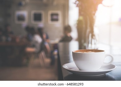 Cappuccino cup on the table with blur people in coffee shop background, vintage tone