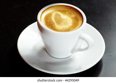 Cappuccino cup in white on a black table with the symbol of the heart in the foam