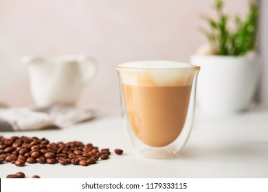 Cappuccino in a double walled glass with roasted coffee beans. Feminine rose background with copy space. High resolution image, narrow depth of field.