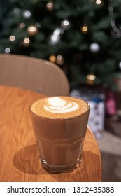 Cappuccino or flat white coffee on table in front of decorated Xmas tree