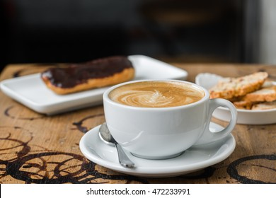 cappuccino flatwhite coffee with eclair on table