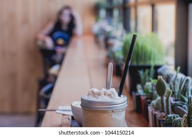 Cappuccino frappe cup on table with Blurred young girl waiting someone in coffeshop.