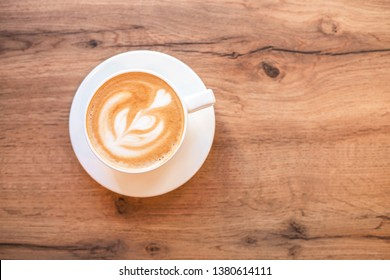 Cappuccino with frothy foam, blue coffee cup top view closeup on white wood background. Flat lay style.