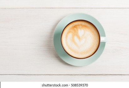 Cappuccino with frothy foam, blue coffee cup top view closeup on white wood background with copy space. Cafe and bar, barista art concept.
