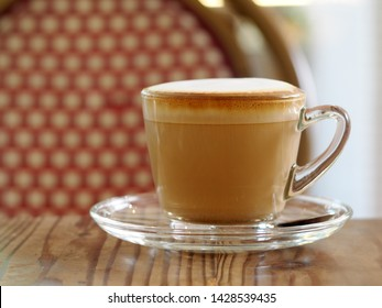 cappuccino with full fine bubble cream little cacao powder served in clear glass coffee cup small size on wooden table warm light tone selective focus blur background in a vintage style cafeteria