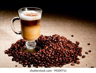 Cappuccino glass with coffee beans on jute