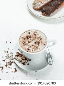 Cappuccino with hazelnuts on a white table and in the corner Traditional French dessert eclair with dark chocolate