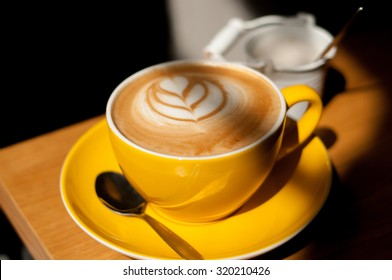 cappuccino with heart in yellow cup on wood table background overhead view cool shadows natural light