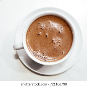 Cappuccino or hot chocolate with frothy foam, white coffee cup top view closeup isolated on white background.