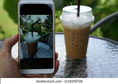 Cappuccino iced coffee Milk froth In the glass on the table background is a tree photography with mobile smart phone