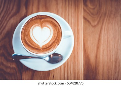 Cappuccino or Latte coffee art cup with heart shaped surface, top view, on wooden table.