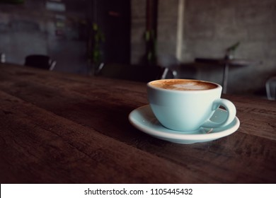 Cappuccino or latte with frothy foam, blue coffee cup top on wooden coffee shop background