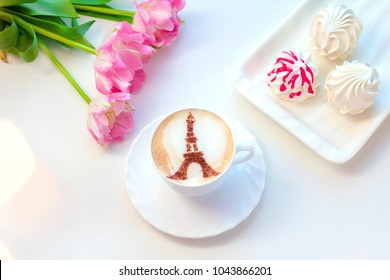 Cappuccino in Paris in a white cup with a pattern of a tower on milk foam with pink tulips and sweet marshmallows