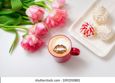 cappuccino in a red cup with a lip pattern with pink tulips and marshmallows