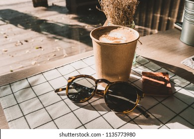 cappuccino in take away coffee cup and sunglasses on table cloth with dry flower on wood table with sunlight hard shadow at window in evening.food and drink lifestyle leisure concept