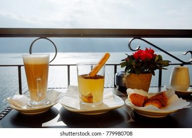 Cappuccino, tiramisu, muffins on the background of the lake