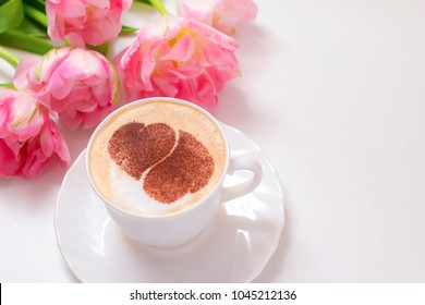 cappuccino in a white cup with a pattern of heart surrounded by tulips and sweet marshmallows