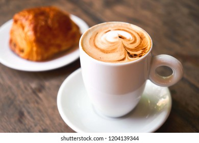 Cappuccino in white cups. Write a heart-shaped on a wooden table with a blurred croissant.Selective focus