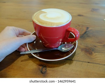 Cappuccino with white milk foam in red cup on wooden table at cafe or at home. Concept for morning routine, mindfulness, coffee addiction or coffee snob. Mormons avoid to drink coffee with caffeine.