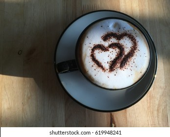 Cappuchino in black cup on wood background