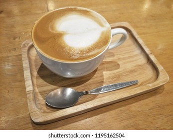 Cappuchino  coffee in ceramic cup and wood Saucer on table.