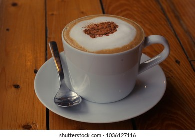 cappuchino coffee in white porcellan cup and saucer with spoon and cinnamon close up photo on wooden table