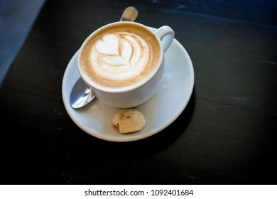Cappuchino or latte coffe in a white cup with heart shaped foam and cookies,morning drink on wooden table.coffee in a white mug on Dark background