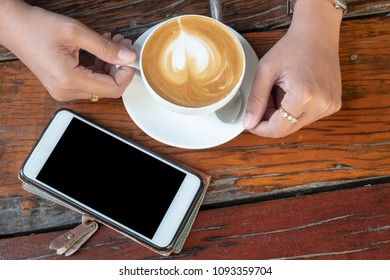 Cappuchino or latte coffe in a white cup with heart shaped foam   on wooden table background and a smatphone near