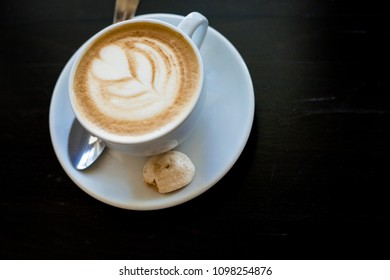 Cappuchino or latte coffe in a white cup with heart shaped foam on wooden board. Morning energy dring isolated on dark background. Copy space. Top view