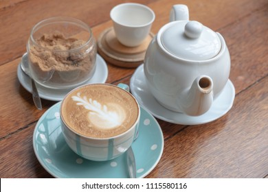 Cappuchino or latte coffe in a white cup with heart shaped foam   on wooden table background