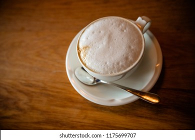 Cappuchino or latte coffe in a white cup with foam on wooden board. Morning energy drink isolated on dark wooden background. Copy space. Top view. Hot drinks.Good morning concept