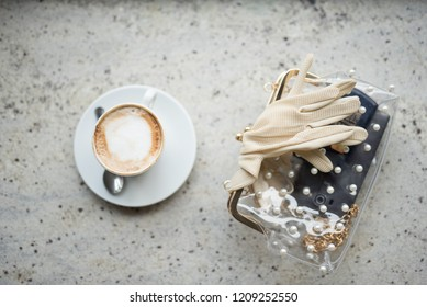 Cappuchino or latte coffe in a white cup with foam on wooden board. Morning energy drink isolated on light wooden background