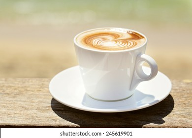 Cappuchino or latte coffe in a white cup  with heart shaped foam on wooden board with ocean on the background