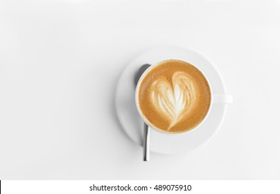 Cappuchino or latte coffe in a white cup with heart shaped foam on wooden board