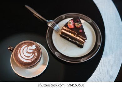 Cappuchino or latte coffe in a white cup on with a cake on a black table.