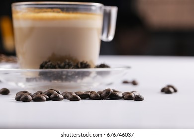 A Cappucino cup and coffee beans on white table