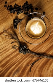 A Cappucino cup and coffee beans on wooden table